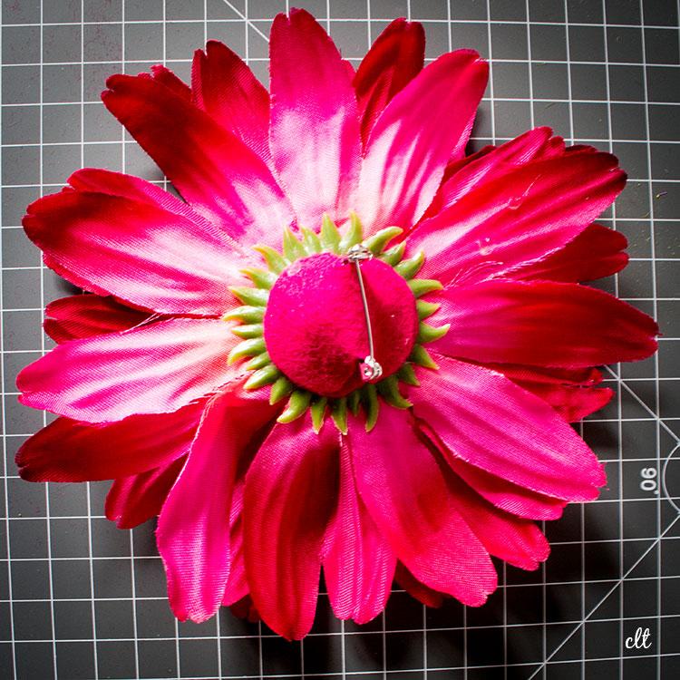 Filz-Kreis mit Broschennadel wird auf angetrockneten Filz auf Deko-Blume geklebt.